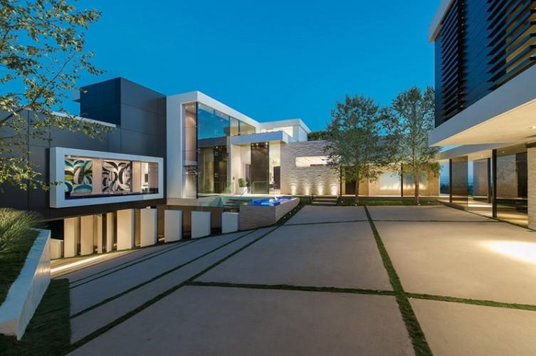 Cours intérieur d'une maison d'architecte carré, grandes vitres et herbe dans le béton