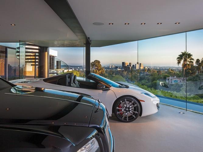 Voitures de luxe dans le salon avec grandes baies vitrées vue sur la ville