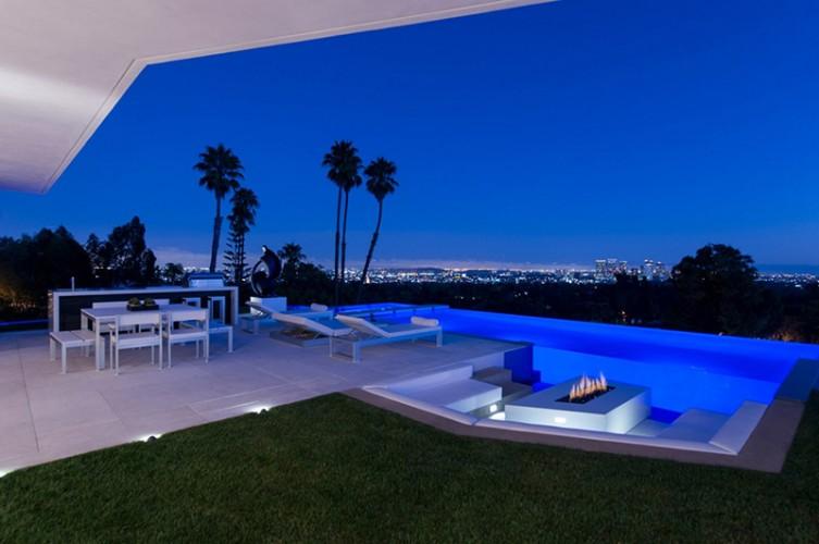 Vue du salon sur piscine et jardin avec transat et palmiers