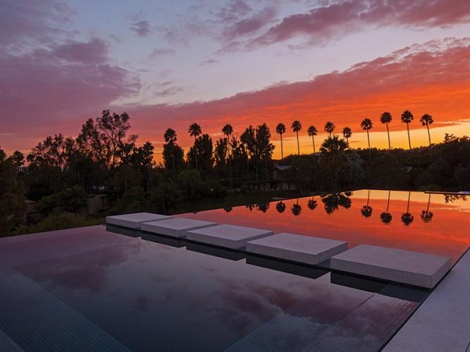 Piscine et palmier qui se reflètent, ciel couché de soleil