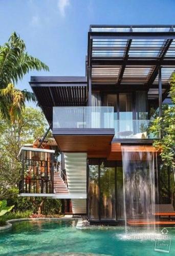 Superbe maison moderne avec garde corps en verre et chute d'eau dans la piscine